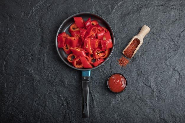 Panela de pimentão vermelho fatiado com pimenta e ketchup