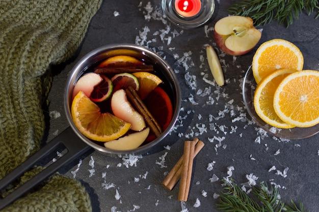 Panela pequena com vinho quente e paus de canela, fatia de laranjas e maçã no escuro