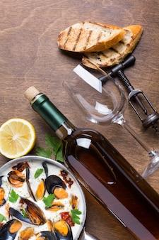 Panela plana com mexilhões em molho branco com garrafa de vinho