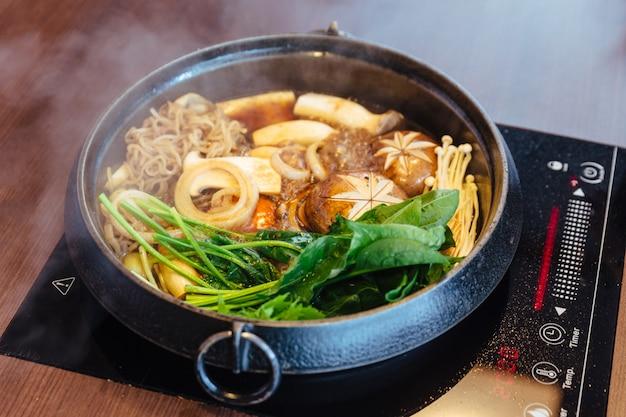Panela quente de sukiyaki com legumes ferventes