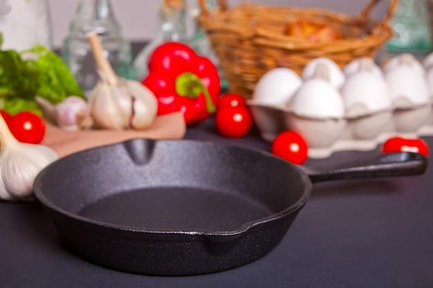 Panela vazia com legumes frescos para cozinhar na mesa escura