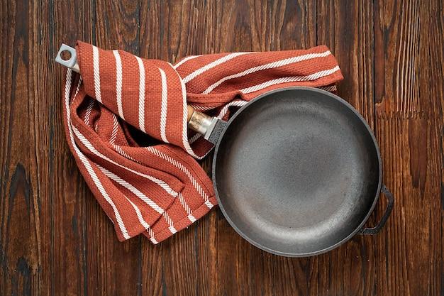 Panela vazia sobre uma mesa de madeira. conceito: cozinhar, cozinha, vista superior