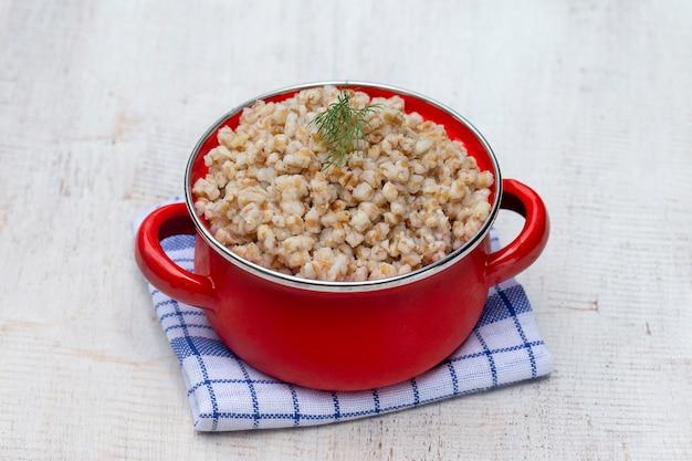 Panela vermelha com mingau de trigo cozido. fechar-se