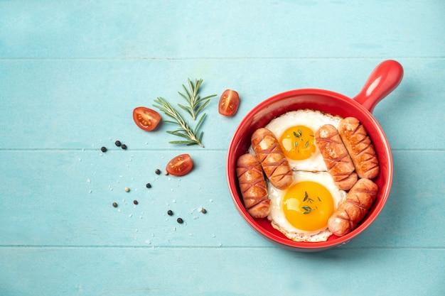 Panela vermelha com ovos fritos e salsichas em azul