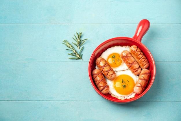 Panela vermelha com ovos fritos e salsichas.