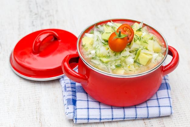 Panela vermelha com sopa tradicional de okroshka de verão