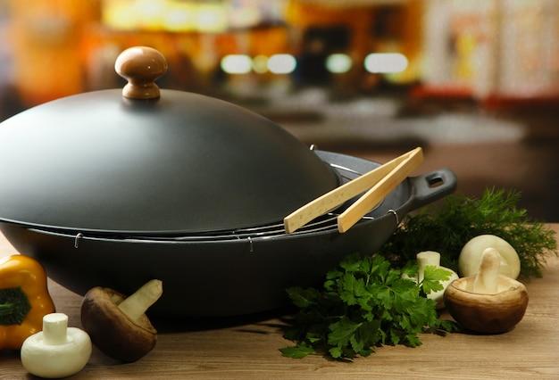Panela wok preta e legumes na mesa de madeira da cozinha, close-up