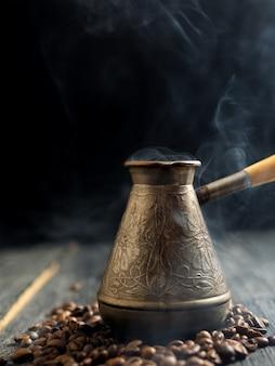 Panelas com café fresco em um fundo escuro com fumaça
