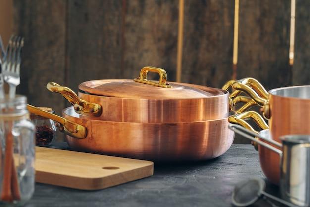 Panelas de cobre com utensílios de cozinha de madeira fechar