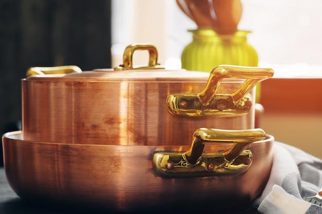 Panelas de cobre com utensílios de cozinha de madeira