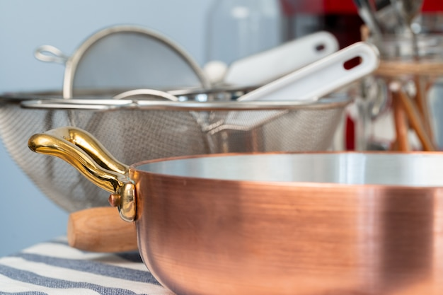 Panelas limpas, utensílios close-up na mesa na cozinha moderna