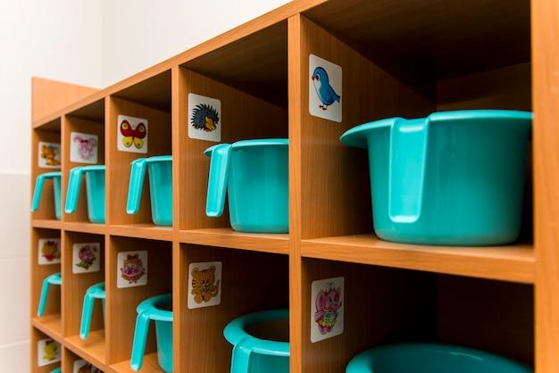 Panelas turquesa infantis enfileiradas em uma prateleira no banheiro do jardim de infância