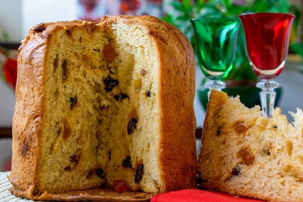 Panetone, fatia de bolo de natal italiano na mesa decorada.