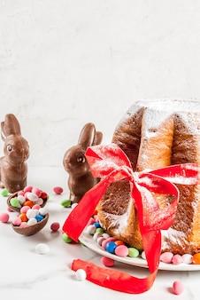 Panetone pandoro com fita vermelha festiva, coelhos da páscoa e decorações de ovos doces