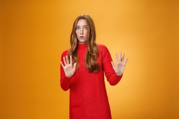 Pânico intenso e garota assustada com cabelo vermelho pedindo para ir devagar, levantando as mãos perto do peito para parar e não gesticular com a boca aberta surpresa e chocada, desanimando oferta estranha sobre fundo laranja