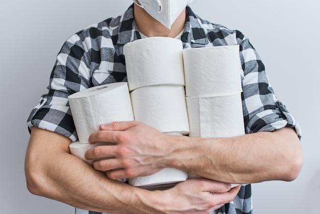 Pânico na compra do consumidor sobre o conceito de coronavírus covid-19. homem segura muitos rolos de papel higiênico