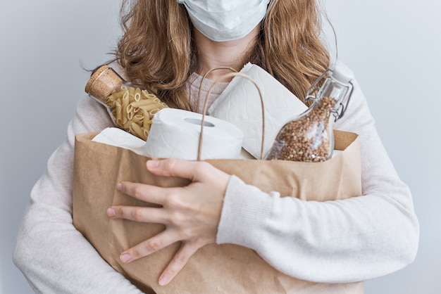 Pânico na compra do consumidor sobre o conceito de coronavírus covid-19. mulher segura sacola com rolos de papel higiênico, macarrão e trigo sarraceno