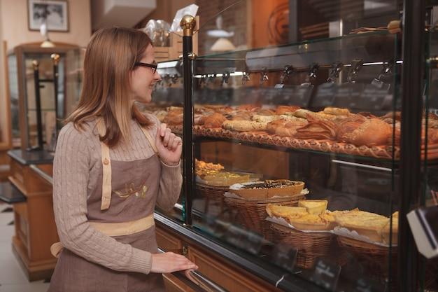 Panificadora orgulhosa examinando a vitrine de sua confeitaria antes de abrir para os clientes