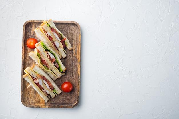 Panini de sanduíche club com presunto, tomate fresco, queijo, em fundo branco, vista de cima com espaço de cópia para o texto