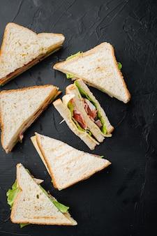 Panini de sanduíche club com presunto, tomate fresco, queijo, em fundo preto, vista de cima