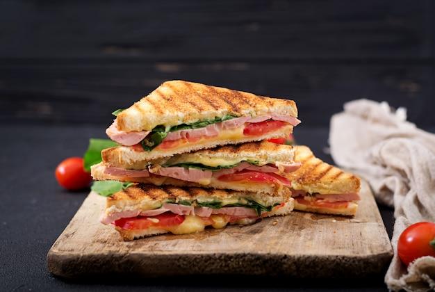 Panini de sanduíche com presunto, tomate, queijo e manjericão.