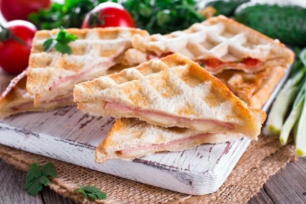 Panini duplo prensado e torrado com presunto e queijo servido em uma mesa de madeira