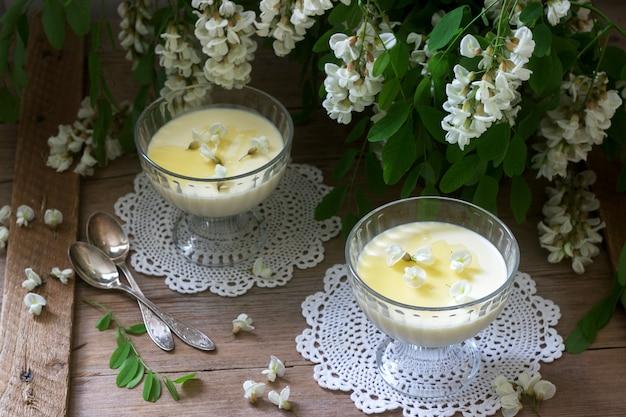 Panna cotta com sabor robinia, servido com mel e flores brancas robinia. estilo rústico.