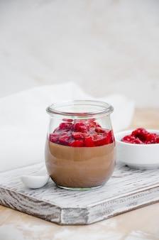 Panna cotta de chocolate com molho de cereja em uma jarra de vidro