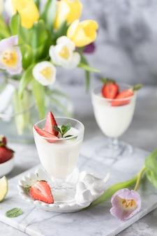 Panna cotta em copos de vidro com morangos sobre um fundo claro. buquê de tulipas em uma mesa branca.