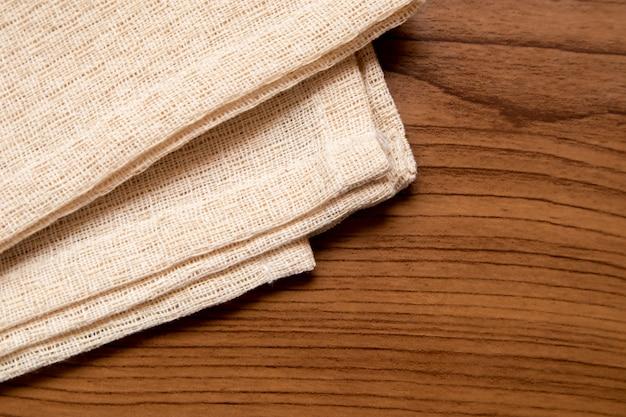 Pano de cor creme na mesa de madeira