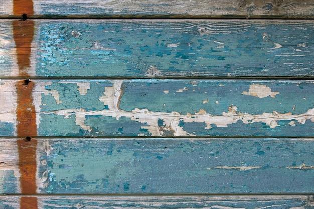 Pano de fundo a tinta azul escura danificada em uma parede de madeira