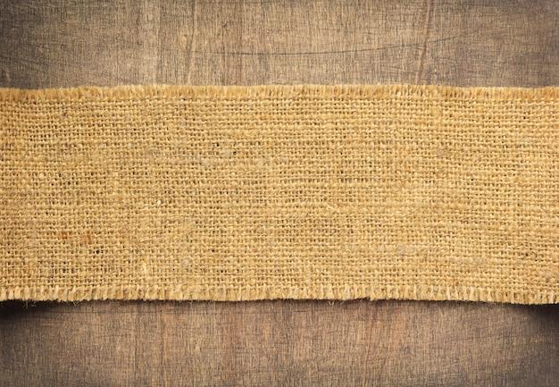 Pano de fundo de saco de juta de serapilheira em fundo de madeira