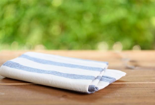 Pano de listras azuis e brancas na mesa de madeira com a natureza verde borrada