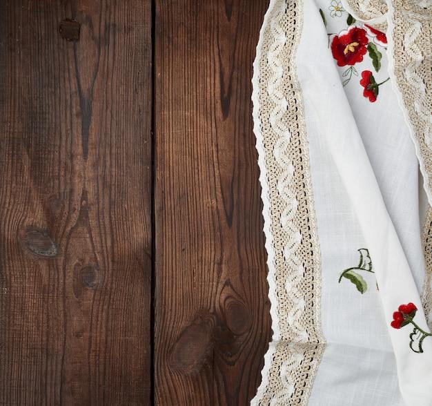 Pano de prato branco bordado com renda sobre uma mesa de madeira marrom
