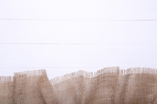 Pano de saco natural no fundo de madeira branco.