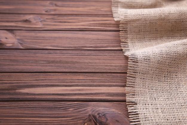 Pano de saco natural no fundo de madeira marrom. lona na mesa de madeira marrom