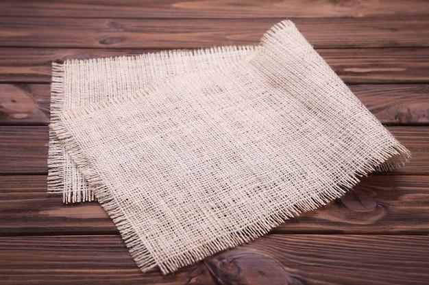 Pano de saco natural no fundo de madeira marrom.