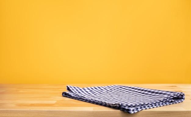 Pano de tecido azul no tampo da mesa de madeira no fundo da parede amarela