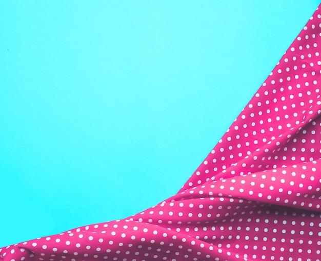 Pano de tecido rosa com pontos com fundo azul. para layout visual chave da decoração