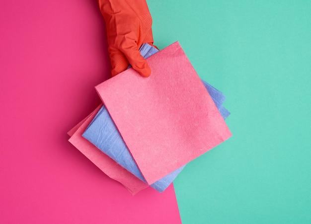Pano de viscose azul para limpar o pó da casa nas mãos com uma luva laranja