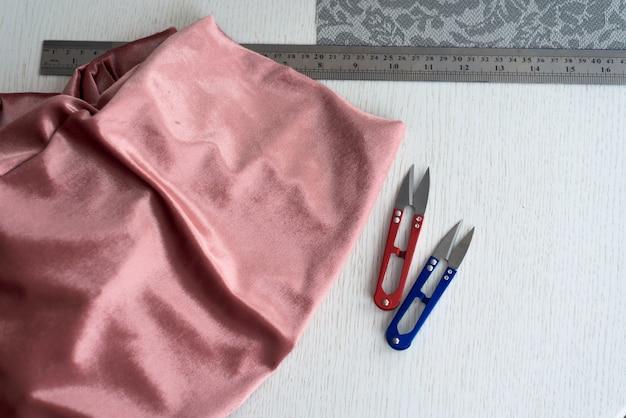 Pano e ferramentas de costura. tesoura alfaiates de diferentes tipos, bobinas com fios.