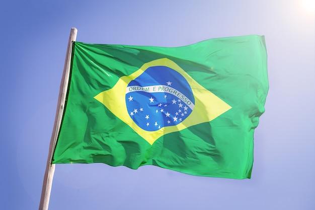 Pano têxtil da bandeira nacional do brasil acenando no topo, céu azul brasil, conceito de patriotismo