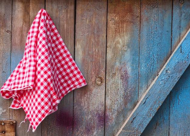 Pano vermelho em uma cela pendurada em uma parede de madeira rachada