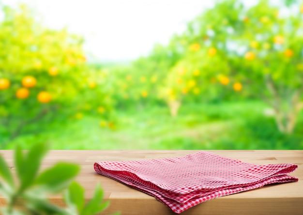 Pano xadrez vermelho sobre mesa de madeira com manchas de jardim laranja