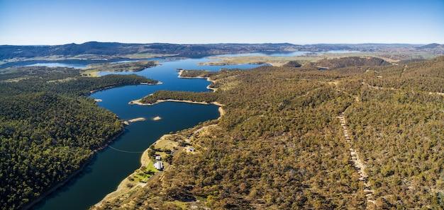 Panorama aéreo do rio nevado que flui entre colinas verdes dos alpes australianos e lago jindabyne