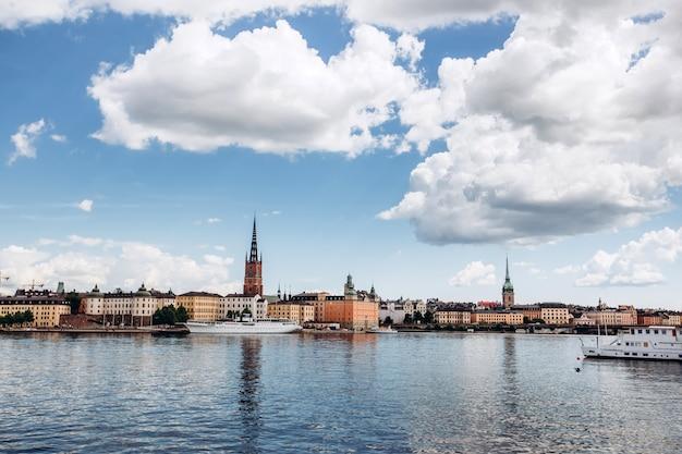 Panorama cênico do verão da arquitetura velha da cidade (gamla stan) em éstocolmo, suécia. vista da colina de monteliusvagen na ilha riddarholm e torre da igreja. lago malaren com céu azul, nuvens brancas.