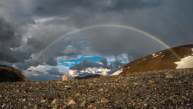 Panorama com um arco-íris e uma pequena casa turística nas montanhas. paisagem alpina atmosférica com montanhas nevadas com arco-íris em tempo chuvoso e ensolarado.