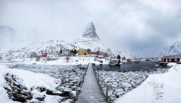 Panorama da aldeia piscatória na montanha íngreme de neve com ponte de madeira