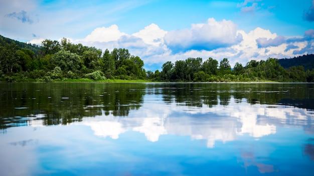 Panorama da bela paisagem com céu azul nublado refletido na água clara