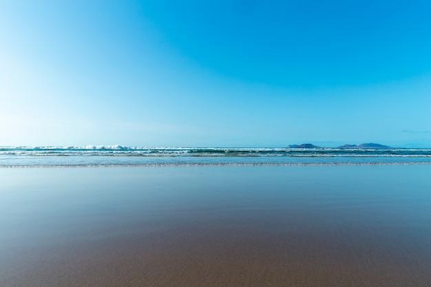 Panorama da bela praia e mar tropical de lanzarote. canárias. costa da praia de famara, ilha de lanzarote, ilhas canárias. turistas na praia mais procurada da ilha de lanzarote.